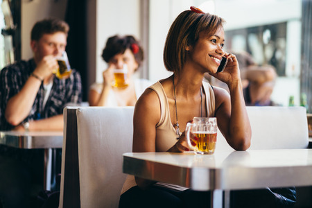 Young woman talking on phone and drinking beer in bar photo