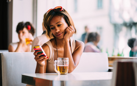 Young black woman texting and drinking beer in bar photo