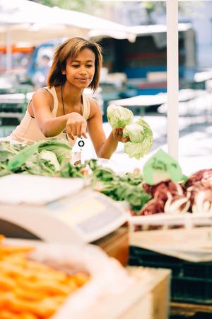농민 시장에서 야채를 구입하는 젊은 여자