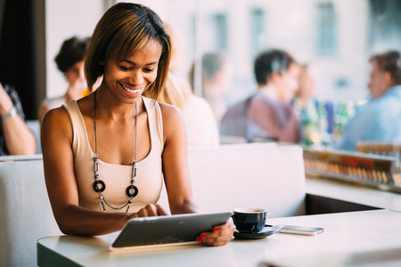 커피 숍에서 태블릿 컴퓨터를 사용하는 젊은 여자