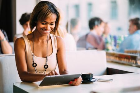 Jonge vrouw met behulp van tablet pc in de coffeeshop