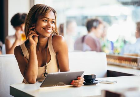 커피 숍에서 태블릿 컴퓨터를 사용하여 젊은 여자