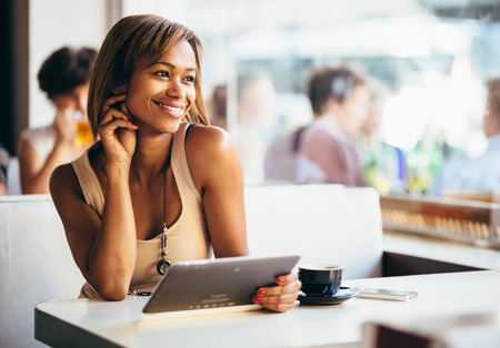 shops: Young woman using tablet computer in coffee shop Stock Photo