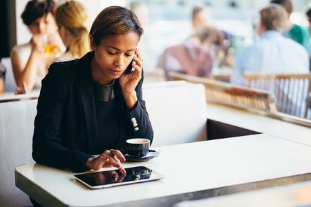 Pensive young businesswoman talking on phone in coffee shop