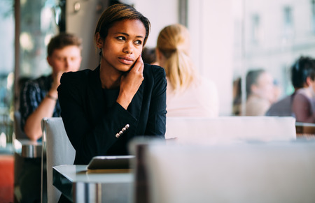 Pensive young black businesswoman talking on phone in coffee shop photo