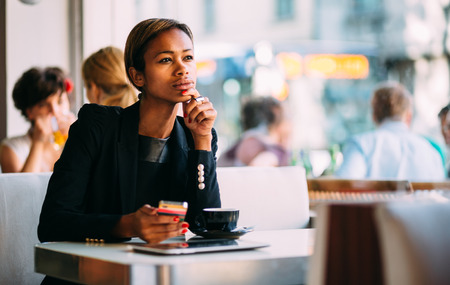 Pensive young businesswoman using smartphone in coffee shop photo