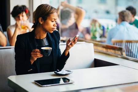 Young businesswoman texting on phone in coffee shop photo