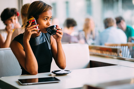 african lady: Young businesswoman talking on the phone in coffee shop