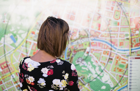 Young woman looking at big tourist city map showing walking distance photo