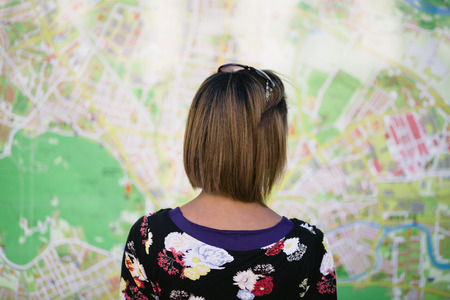 Young woman looking at big tourist city map photo