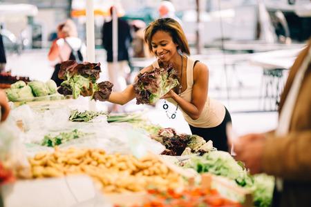 若い黒の女性の農民市場で野菜を買う