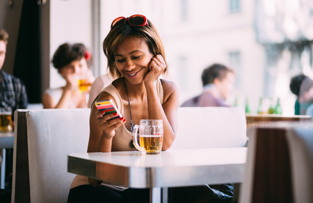 woman bar: Young black woman texting and drinking beer in bar Stock Photo