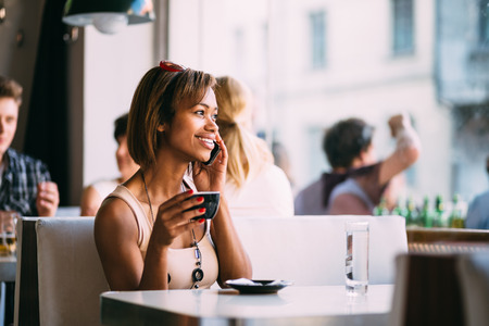 Young black woman talking on the phone in coffee shop photo