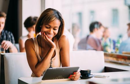 若い黒人女性のコーヒー ショップでタブレット コンピューターを使用して