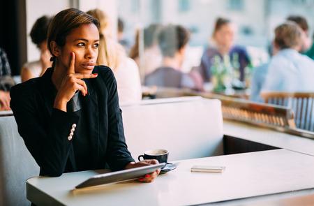 mujer pensativa: Negro mujer joven pensativo con tablet PC en la cafetería Foto de archivo