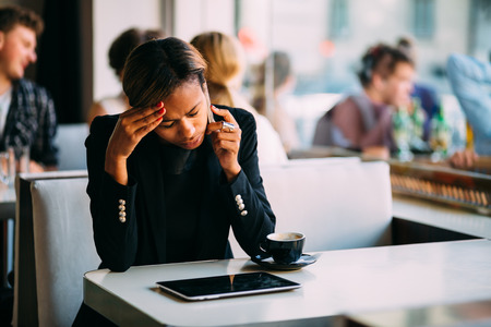 Stressed young businesswoman talking on the phone in coffee shop