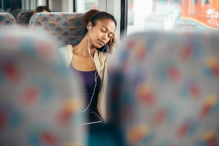 sleeping tablets: Young woman listening to musing and sleeping on train Stock Photo