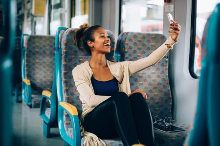 mujeres africanas: Mujer joven tomando un selfie en el tren con su teléfono Foto de archivo