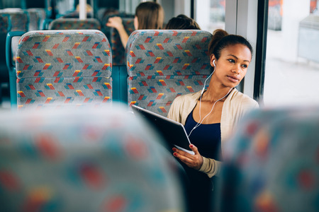 Mujer joven que escucha la música en el tren con tablet PC Foto de archivo