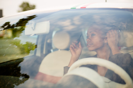 Young black woman applying mascara in car photo