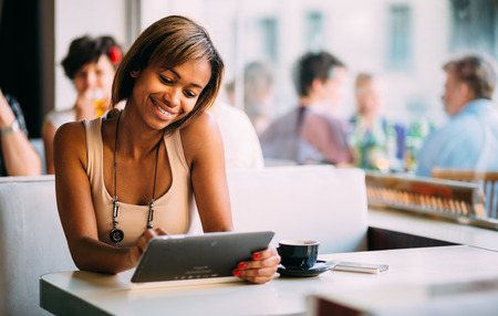 Young black woman using tablet computer in coffee shop photo