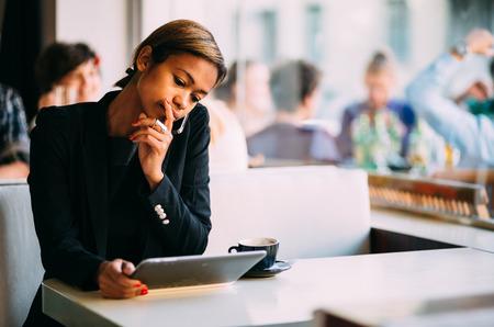 Peinzend zwarte zakenvrouw met behulp van tablet pc in de coffeeshop