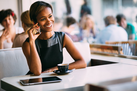 Young black businesswoman talking on the phone in coffee shop photo
