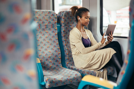 Young black woman listening to music on train using tablet computer Stockfoto