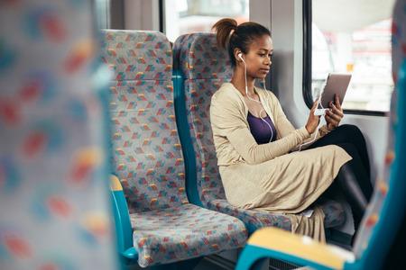 Mujer negro joven que escucha la música en el tren con tablet PC