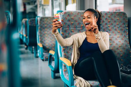 彼女の電話で電車の中で、selfie を取る若い女性
