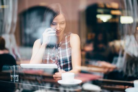 ライフスタイル: コーヒー ショップに電話で話している若い女性 写真素材
