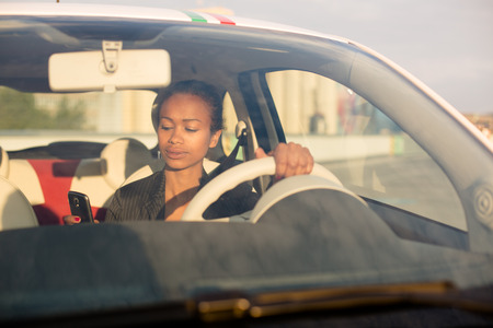 Young black businesswoman texting in car photo
