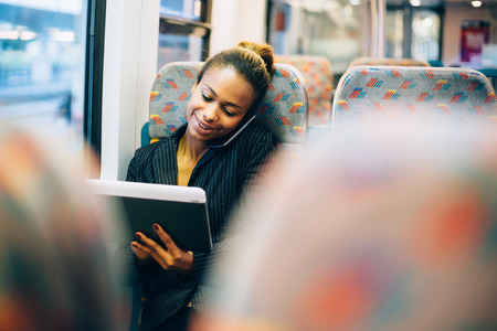 subway train: Young businesswoman talking on the phone and using tablet computer on train Stock Photo