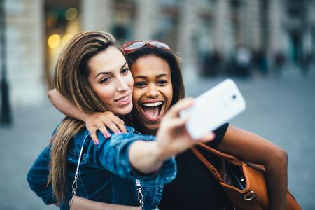tomar: Multi Amigos étnicos se divertindo na cidade tomada selfie