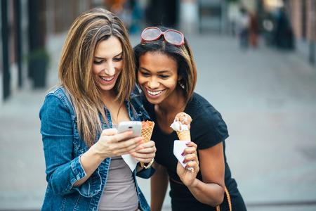 多民族の友人市やテキスト メッセージで、アイスクリームを食べる