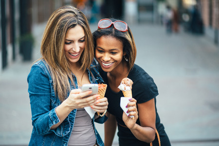 american city: Multi ethnic Friends eating ice cream in city and texting