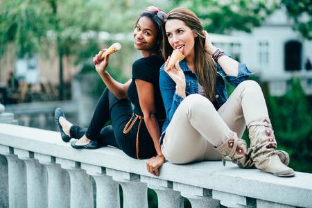 Multi ethnic Friends eating ice cream in city photo