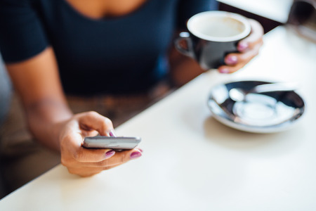 Young black woman using phone in coffee shop photo