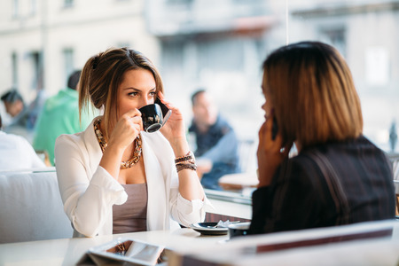 Multi ethnic businesswomen talking on phone in coffee shop photo