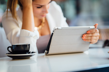 Young businesswoman using tablet computer in coffee shop photo