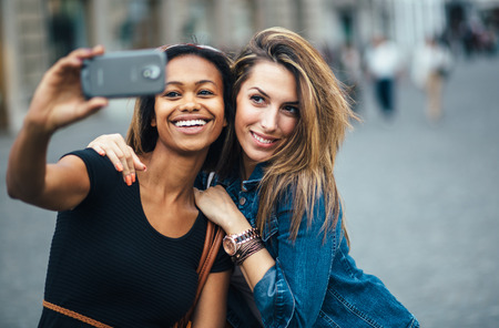 Multi ethnic Friends having fun in city taking selfie photo