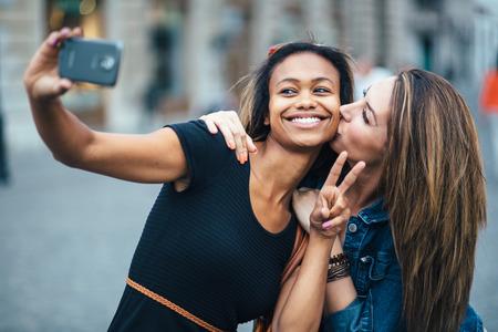 young black girl: Multi ethnic Friends having fun in city taking selfie