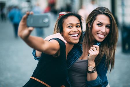 Multi ethnic Friends having fun in city taking selfie