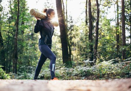 Jonge vrouw die in bos gewichtheffen Stockfoto