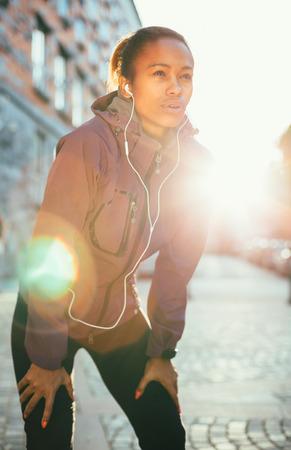 sudando: Mujer cansada joven que coge aliento despu�s de una larga carrera en la ciudad