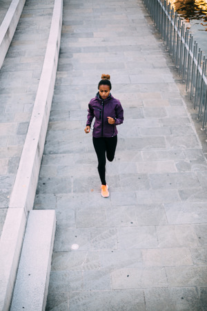 Young woman running in the city on river bank photo