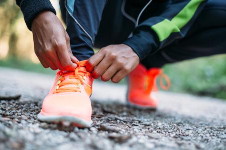 アスリート: 若い女性のトレーニングの前に実行している靴のひもを結ぶ 写真素材