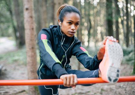 afroamericanas: Corredora joven que estira en el bosque