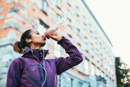 市内を走る後水を飲む若い女性 写真素材