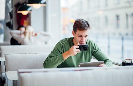 若い男が通りにタブレット コンピューターを使用しながらコーヒーを飲む